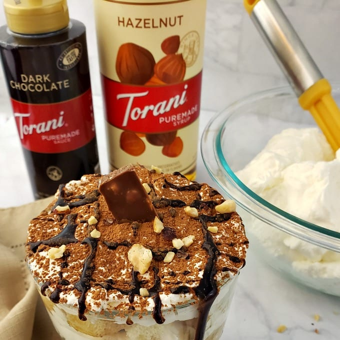 A close up of a Tiramisu Cup dessert drizzled with chocolate and dusted with cocoa powder. A bottle of Torani Puremade Dark Chocolate Sauce and Torani Puremade Hazelnut Syrup next to a bowl of whipped cream in the background.