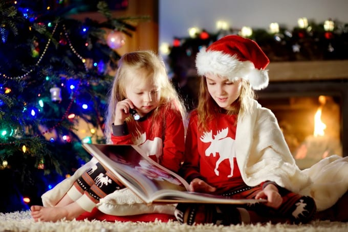 create meaningful traditions with your kids - two girls reading a book in front of a decorated Christmas tree