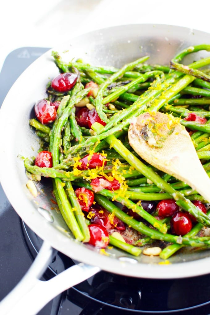 pan seared asparagus with orange zest, toasted nuts, and fresh cranberries in a skillet with a wooden spoon