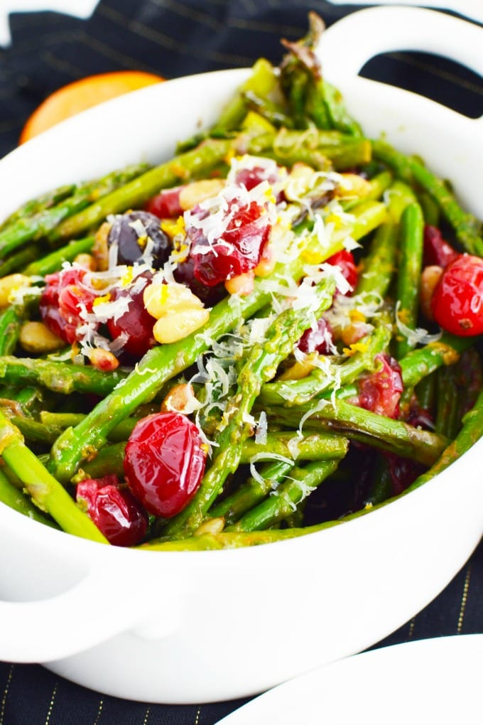 A white serving dish of asparagus with toasted pine nuts, fresh cranberries and garnished with Parmesan cheese