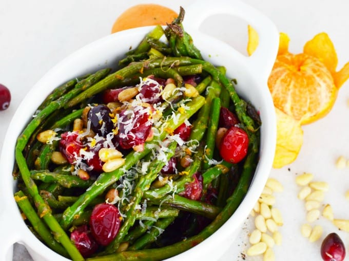 A white serving dish of asparagus with toasted pine nuts, fresh cranberries and Parmesan cheese