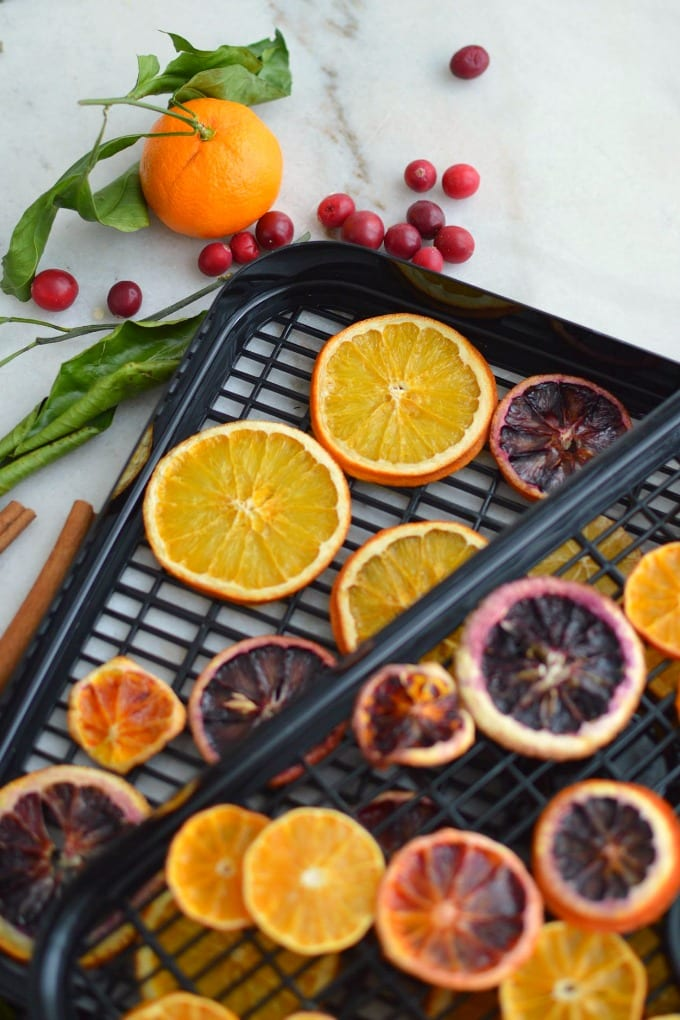 Beautiful dried orange slices for ornaments are a wonderful way to add homemade rustic charm to your holiday decor this Christmas! Get step-by-step instructions for drying citrus in the oven or using a dehydrator. Add to garland and wreaths or make ornaments. #ad #tutorial via @jugglingactmama
