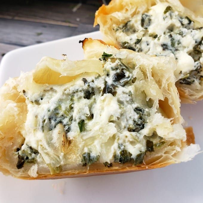 Golden brown Spinach Puff Pastry appetizer cut in half to reveal a cheese, chicken and spinach filling on a white serving tray.