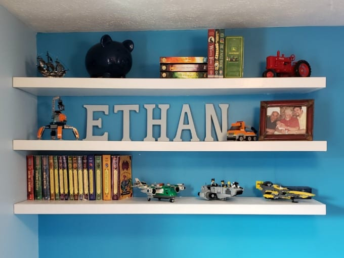 White DIY Floating Wood Shelves against a bright blue wall with books and toys.