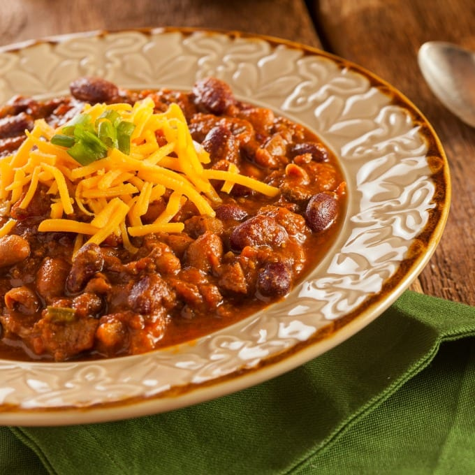 Sweet and Spicy Chili Recipe - two bowls of chili topped with cheese and green onions on a wooden table.