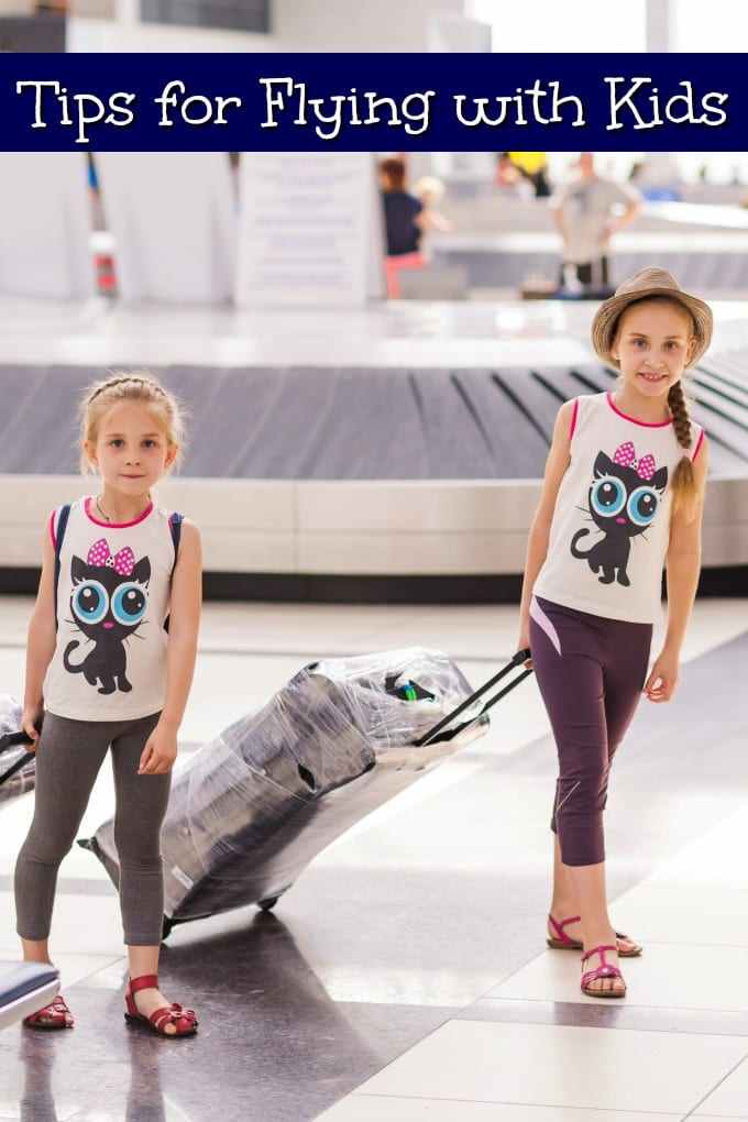 Two girls in an airport with luggage - Tips for Flying with Kids