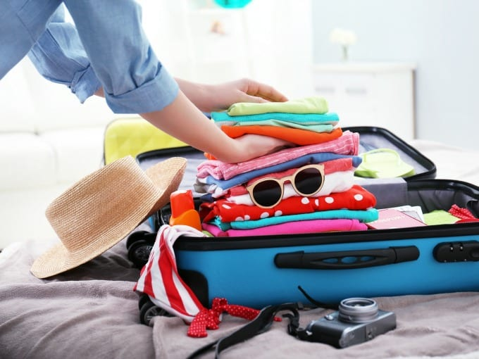 woman packing a suit case with clothes, hat, sunglasses and camera