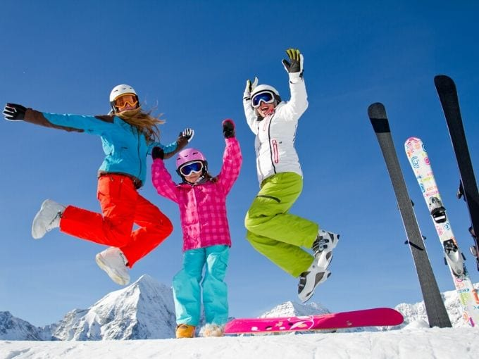 Three girls dressed in bright colored snow pants and ski jackets jumping with lots of joy on their faces
