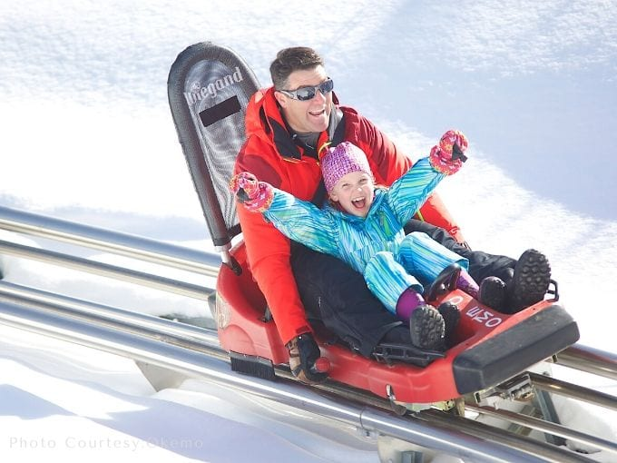 a dad and a little girl with their winter clothes on as they enjoy the thrill of ride on mountain coaster