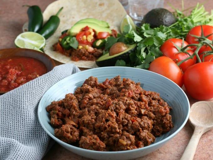 ground beef taco meat in a bowl surrounded by taco ingredients.