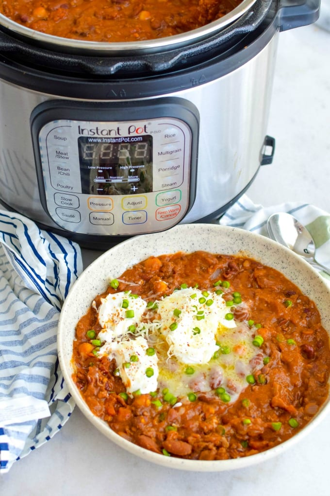 Instant Pot Beef Chili topped with sour cream and green onions next to an Instant Pot.