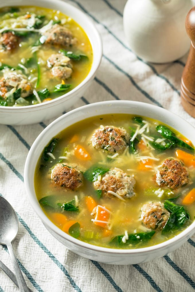 Slow Cooker Italian Wedding Soup loaded with Italian meatballs, spinach and carrots is so hearty and delicious. It is perfect for a chilly night! via @jugglingactmama