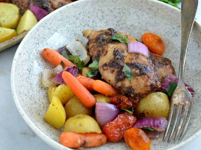 close up of Sheet Pan Balsamic Chicken dinner in a bowl with a fork