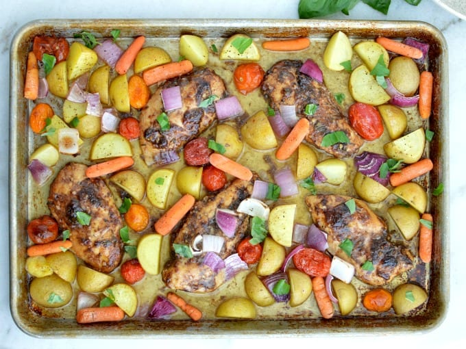 top down view of a Sheet Pan with Balsamic Chicken, golden potatoes, red onions, tomatoes and carrots