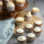 Carrot cupcakes with a cream cheese frosting topped with walnuts next to a blue cloth napkin.