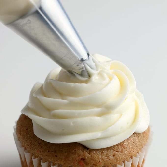 a piping bag fitted with a star tip adds the best cream cheese frosting recipe to the top of a cupcake.