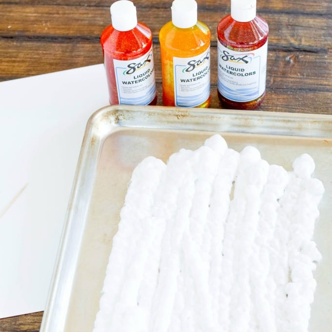 three bottles of paint and a baking sheet covered with shaving cream used for shaving cream painting project
