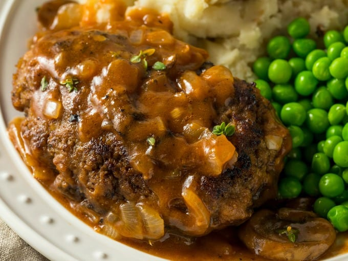 close up of plated Homemade Salisbury Steak Recipe with potatoes and peas