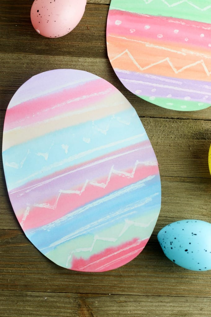 Using wax to draw on Easter eggs is a fun way to create unique designs on each of your eggs. This simple art project uses the same concept to turn plain white paper into pretty pastel Easter artwork. via @jugglingactmama