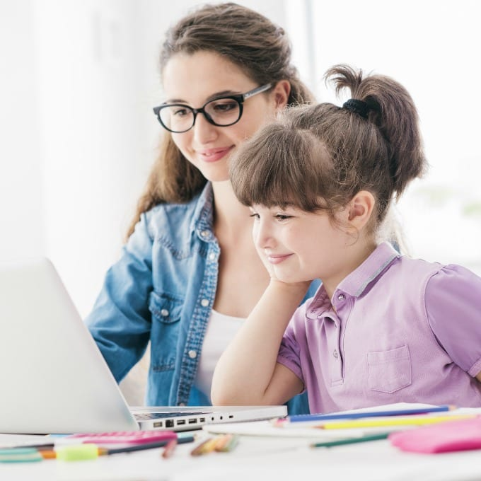 Teen and young girl looking at a laptop while remote learning.