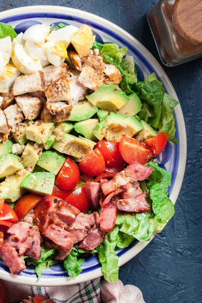 Close up of a cobb salad with grilled chicken, avocado, bacon, tomato, red onion, blue cheese and eggs.
