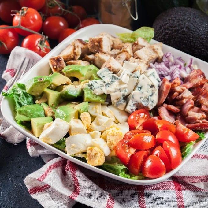 Healthy cobb salad with chicken, avocado, bacon, tomato, and eggs. American dish