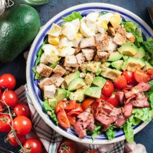 Close up of a chicken cobb salad with avocado, bacon, tomato, red onion, blue cheese and eggs.