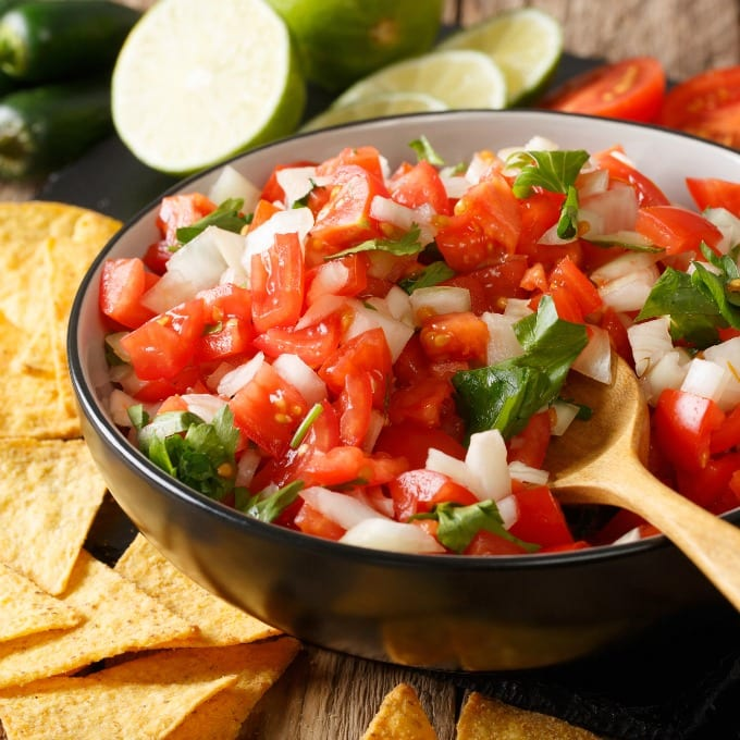 Close up of Easy Pico de Gallo - tomatoes, onions and cilantro in a bowl with spoon surrounded by tortilla chips, sliced limes and  halved tomatoes.