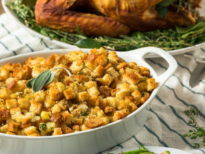 Cornbread Sausage Stuffing Recipe - close up of cornbread sausage stuffing in a white baking dish on a table with a turkey in the background.