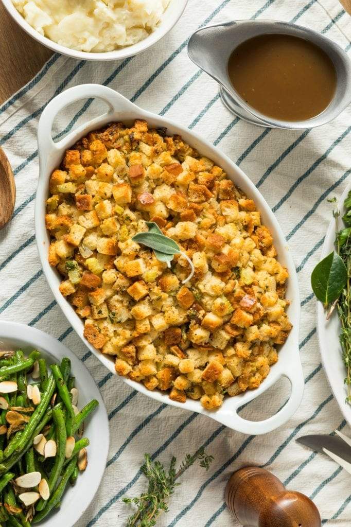 How to Make Cornbread and Sausage Stuffing- top down view of up of cornbread sausage stuffing garnished with fresh sage in a white baking dish on a Thanksgiving table set with mashed potatoes, gravy and green beans.