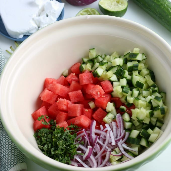 Mixing bowl filled with the ingredients for watermelon salad - watermelon, cucumber, mint, and red onion.