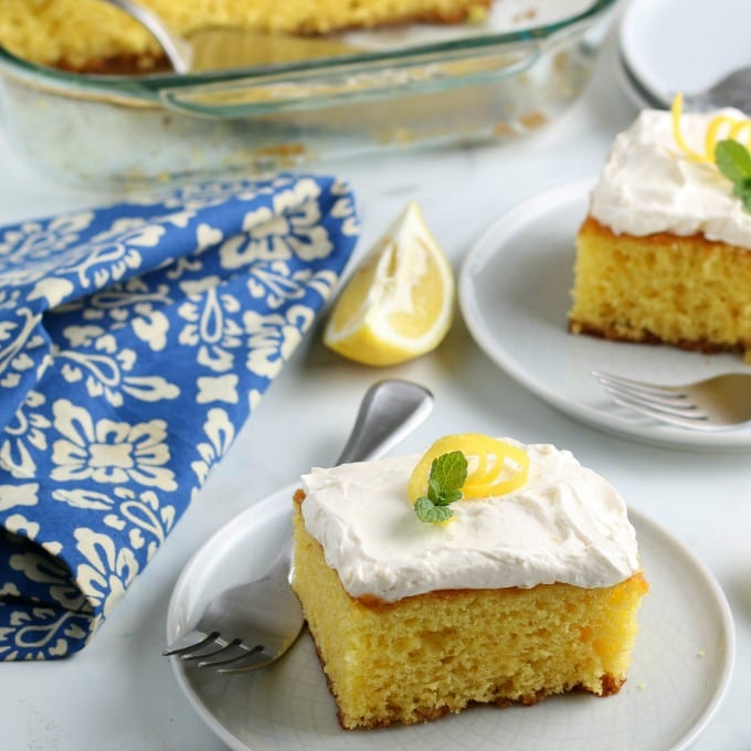 slices of lemon cake garnished with mint leaves and lemon zest on white plates. In the background is the baking dish with the rest of the cake
