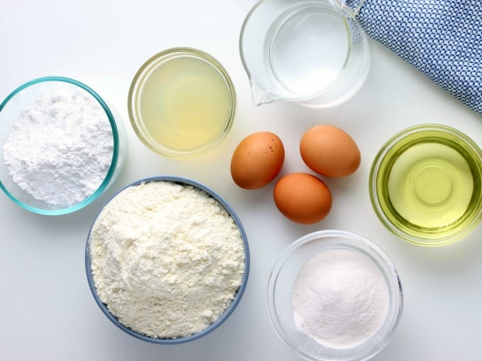 Ingredients for How to Make Lemon Cake including bowls of cake mix, lemon juice, water, oil and powdered sugar as well as three brown eggs.