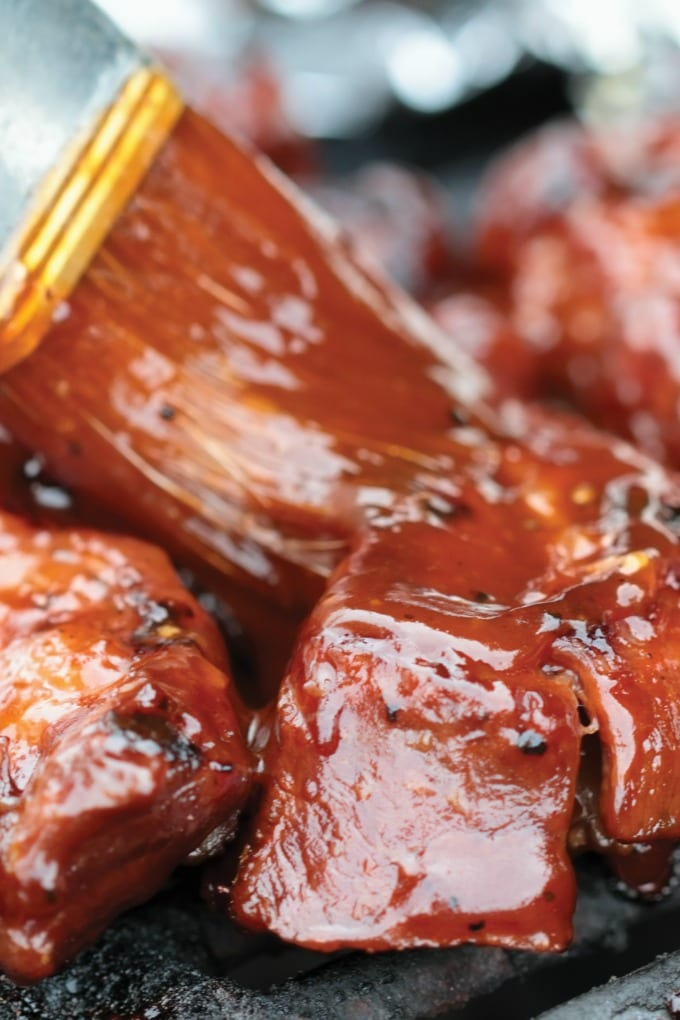 Image of ribs on the grill be brushed with Cherry BBQ Sauce.