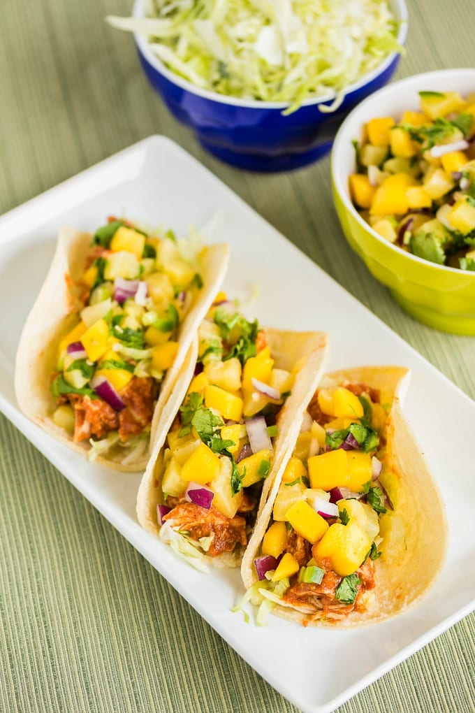My BBQ Chicken Tacos recipe combines two of my favorite recipes - fresh mango salsa, and a delicious slow cooker BBQ chicken. You will love this recipe! via @jugglingactmama