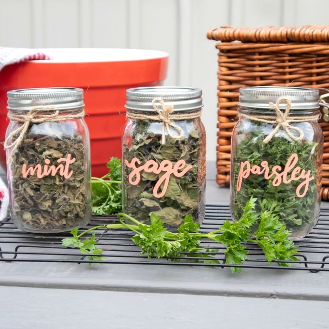 Three Cricut diy dried herb mason jars labeled with the words mint, sage, and parsley. Twine is wrapped around the neck of each jar. There is a large red bowl and a picnic basket in the background.