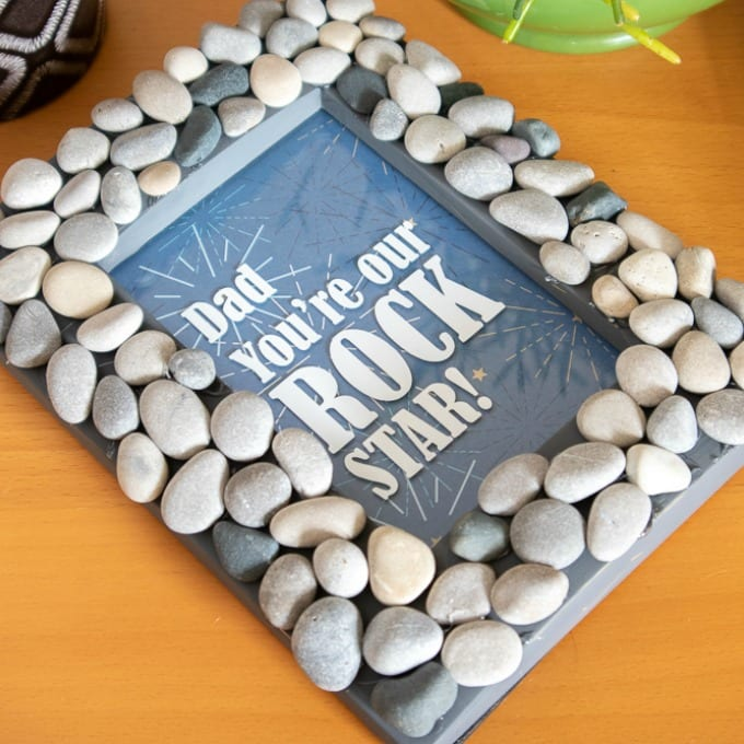 Finished Cricut Photo Frame covered in rocks laying on a table top.