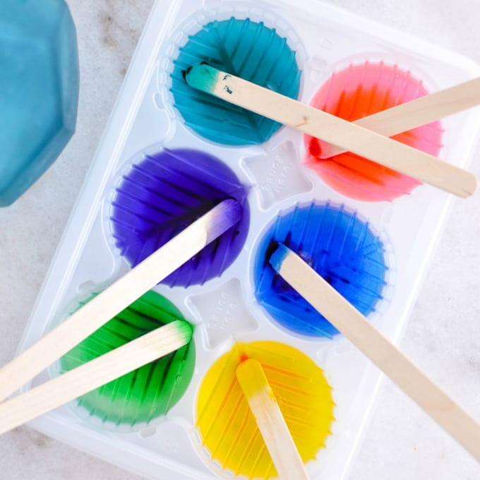 Colored water and popsicle sticks in a white plastic muffin tin.