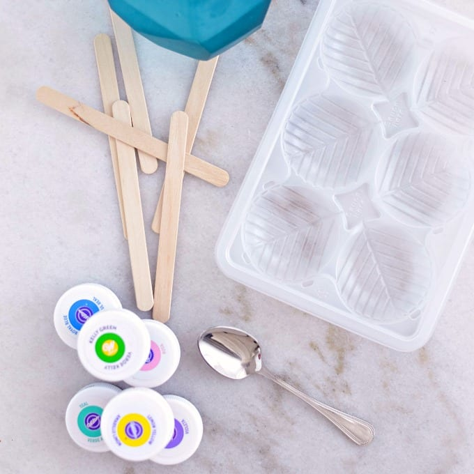 close up of an ice cube tray, craft sticks and food coloring to make colored ice cubes for painting