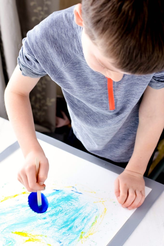Painting with Ice Cubes - a young boy paints with a blue ice cube on a craft stick.