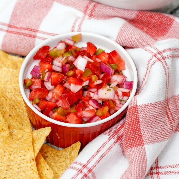 Ramekin of fresh homemade strawberry salsa surrounded by chips and a towel