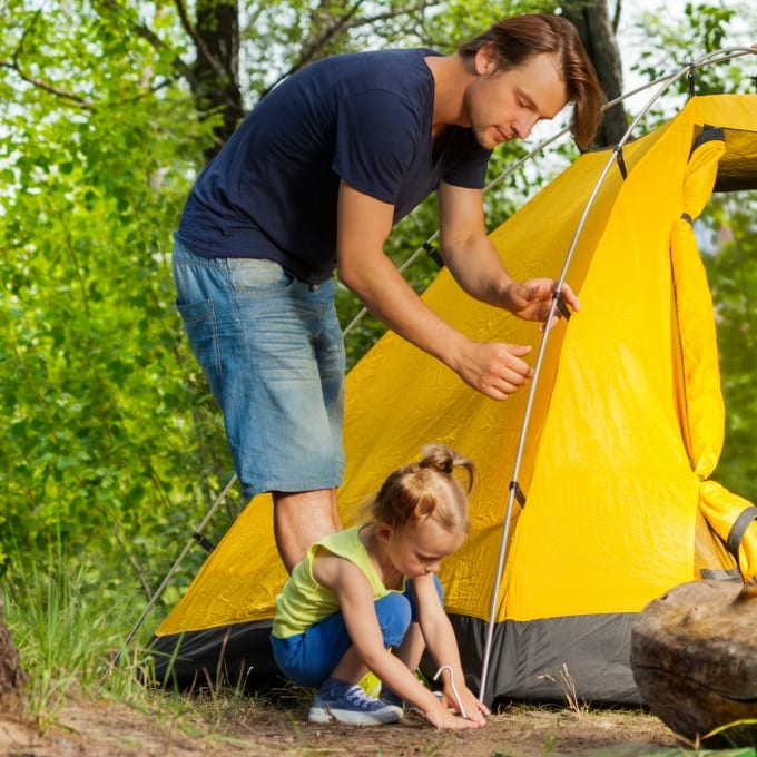 backyard camping ideas - dad and little girl setting up a yellow tent for camping