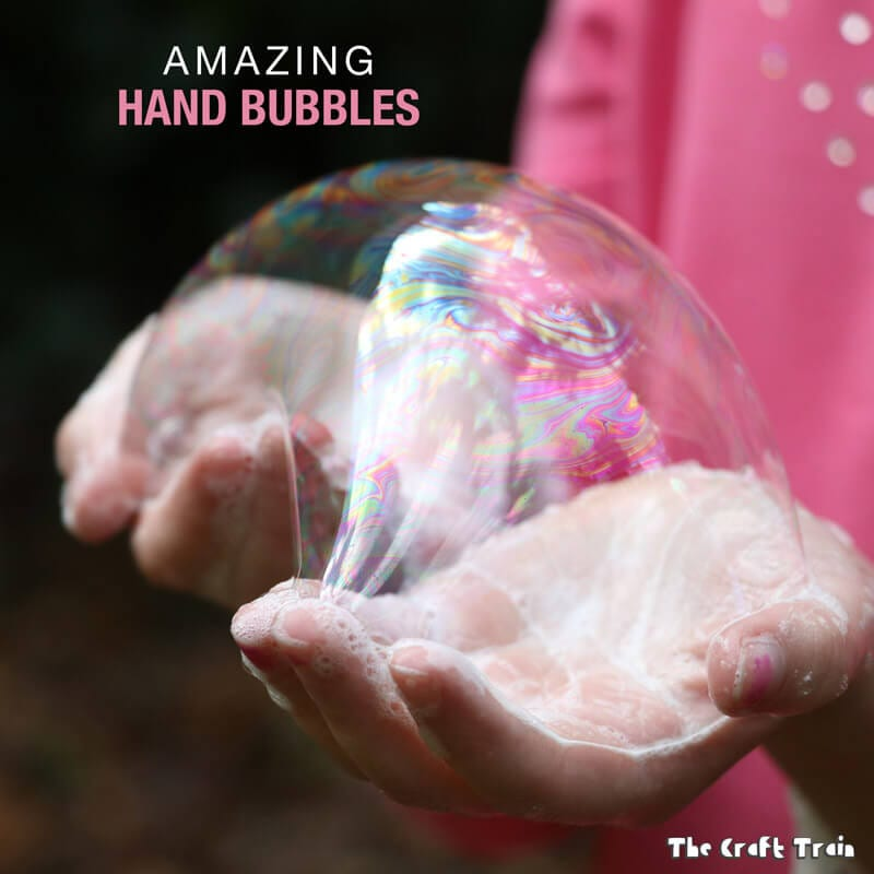 Bubbles and suds sitting on a child's hands.