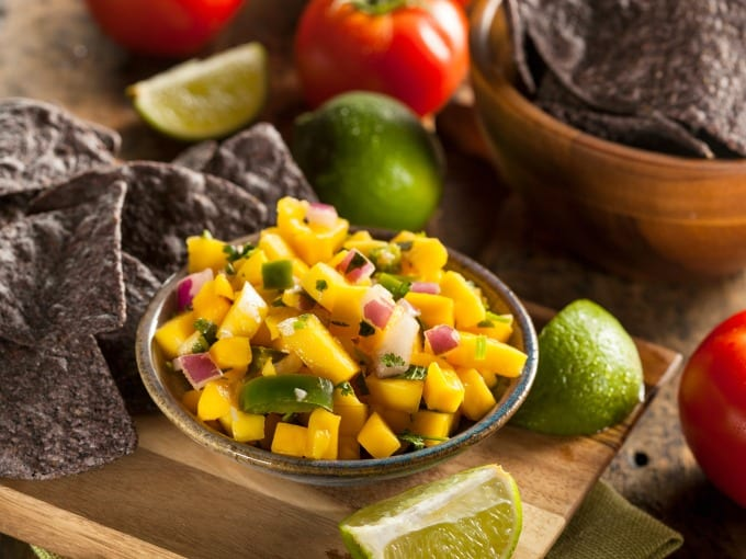 Fresh homemade mango salsa in a ceramic bowl sitting atop a wooden cutting board surrounded by lime slices and blue corn chips.