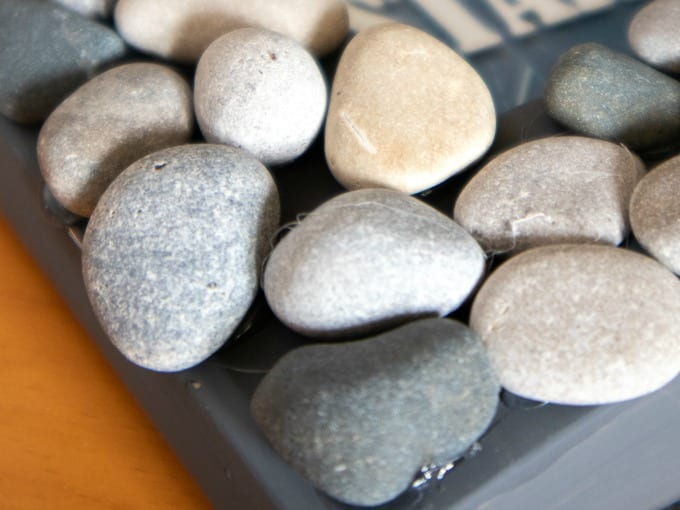 Image contains a close up of small rocks hot glued to a gray painted picture frame.