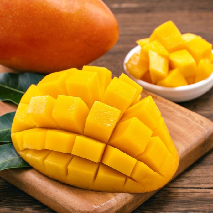 Fresh chopped mango cubes on wooden cutting board