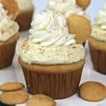 Square, close up image of a banana pudding cupcake on a white platter with NIlla wafers.