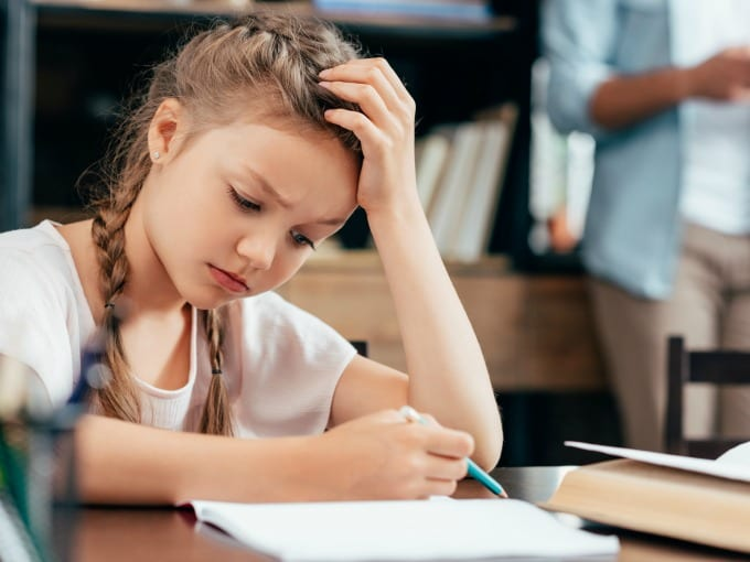 Young girl that looks anxious while working on school work.