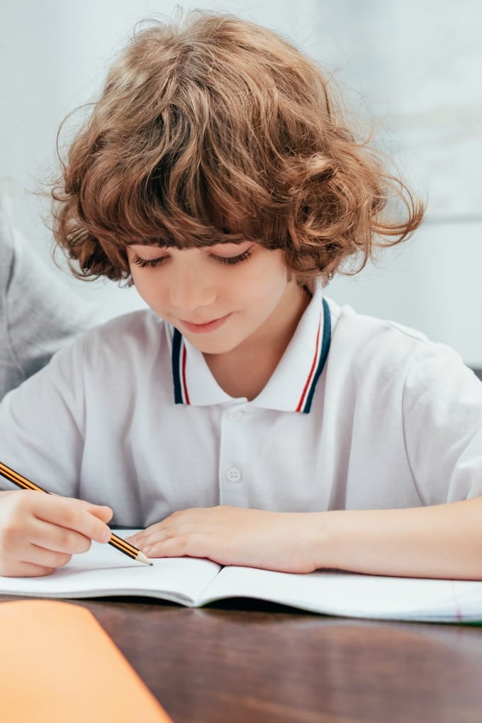 Young boy writing in a notebook while remote learning.