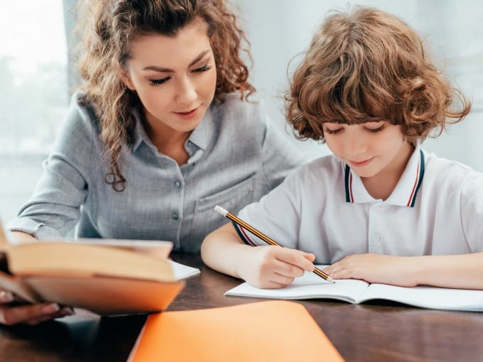 Young boy sitting at a table with his mother while working on school work.